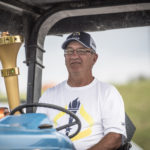 Bill Wirthwein carries the torch into the town of Santa Claus on his tractor from Pumpkins & More.