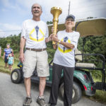Pat Koch and Wayne Utley pass the torch on the west side of Santa Claus, Indiana.