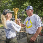 Steve Haaff passes the Bicentennial Torch to Connie Luthy outside of Lincoln Boyhood National Memorial.