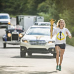 At a cross country pace, Sienna Crews runs the torch through Lincoln City and into Gentryville.