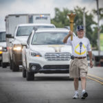 George Meece, a longtime resident of Chrisney, proudly walks the torch down Main Street.