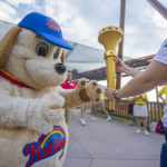 Holidog takes the torch from Torchbearer Lauren and carries it out of Holiday World to prepare for the next stop.