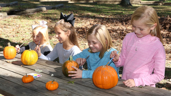 Children painting pumpkins for Halloween outside at Lincoln State Park