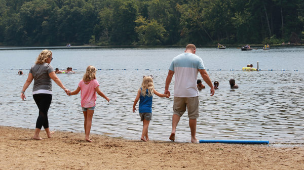 Parents and two children walking across beach toward lake