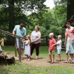 Parents and children interacting with costumed interpreter in cabin yard at Living Historical Farm inside Lincoln Boyhood National Memorial