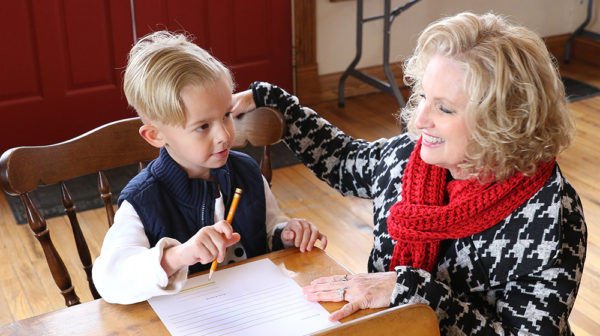 Little boy with blond hair sits at a desk with a pencil in hand and letter on desk. Blond woman squats next to the desk and rests right hand on back of chair.