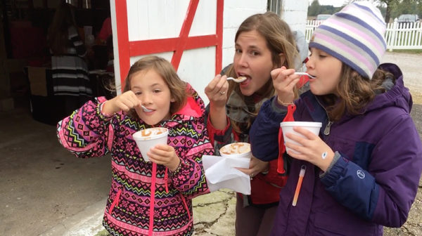 Adult woman and two girls in winter clothing, each taking a bite from a spoon